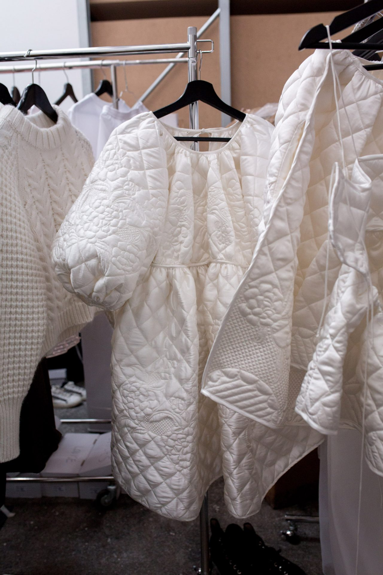 White quilted dresses hanging backstage from Cecilie Bahnsen AW18.