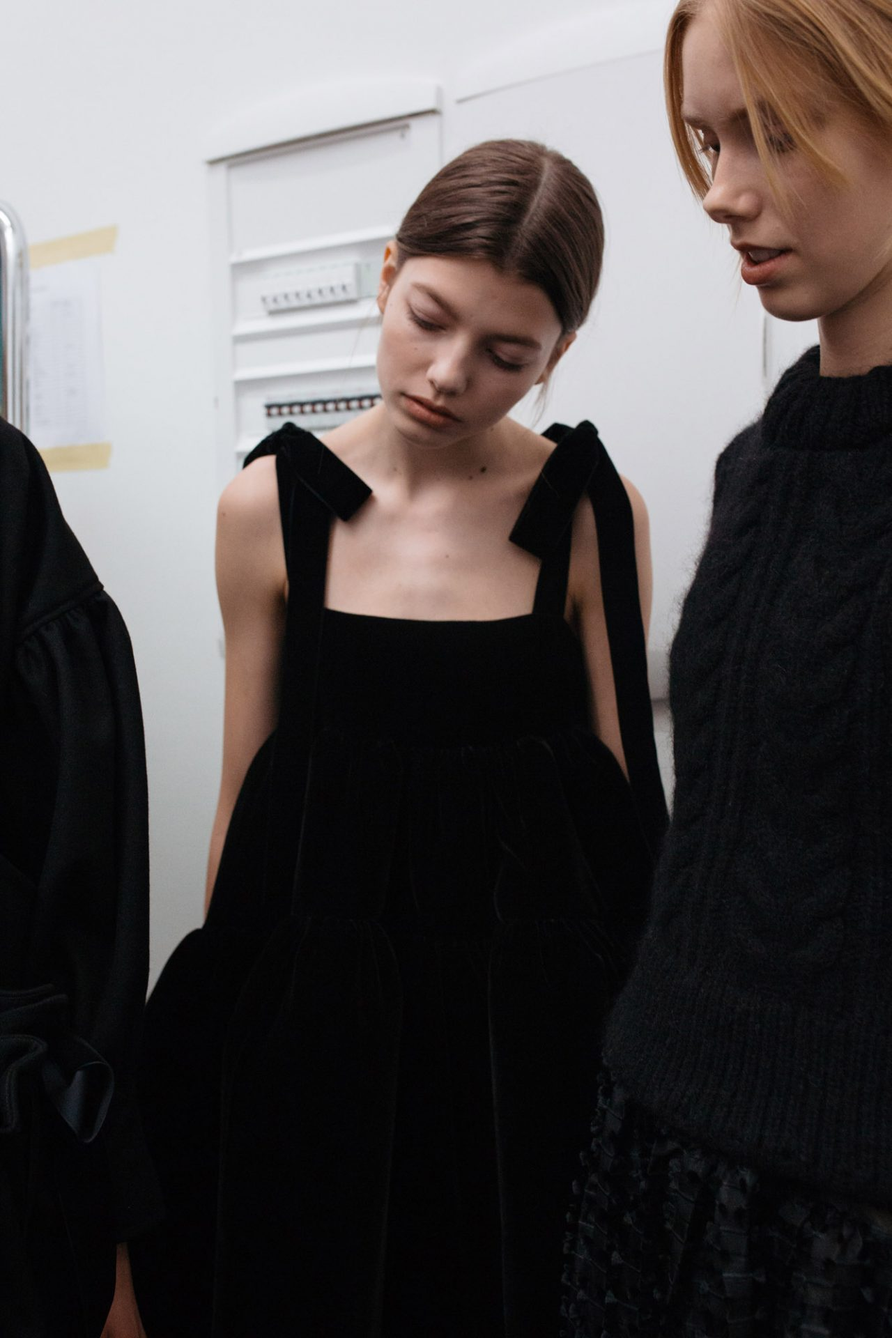 Model in black dress with bow straps backstage at Cecilie Bahnsen AW18. The Cutting Class.