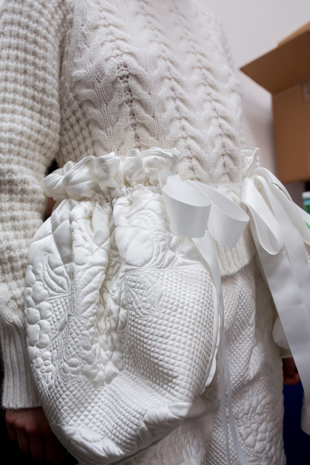 Sumptuous Quilting at Cecilie Bahnsen | The Cutting Class. White quilted satin shorts worn with knitwear.