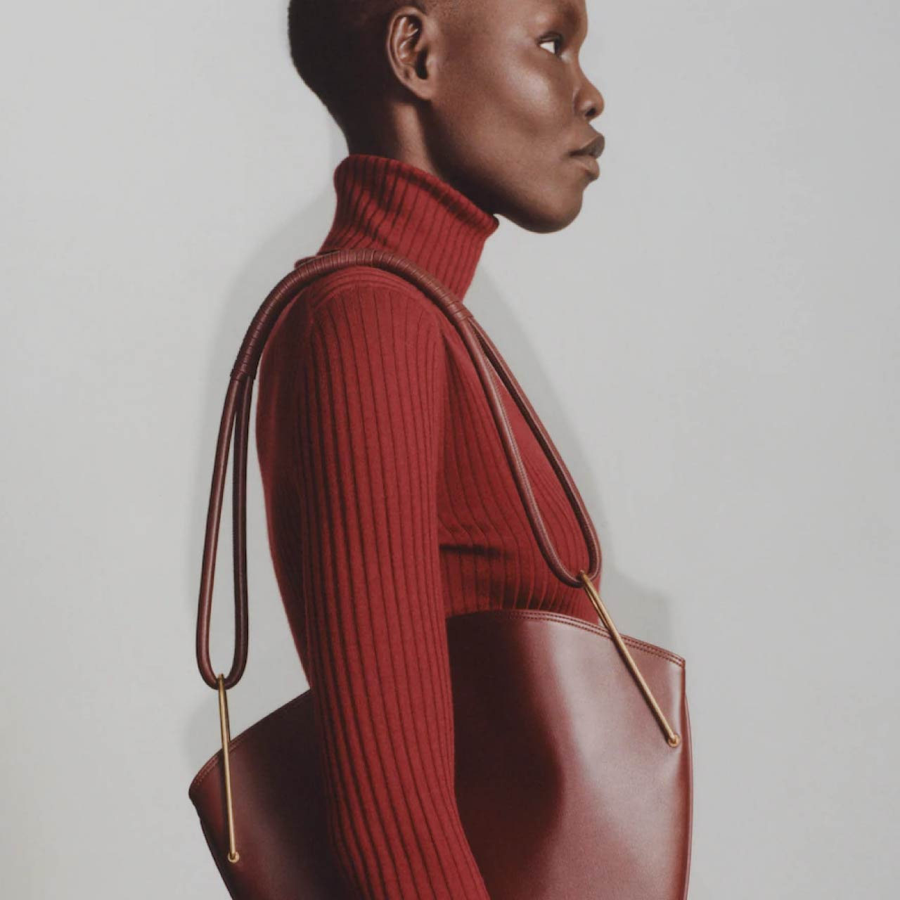 Slight Dropped Shoulders at The Row | The Cutting Class. Pre Fall 2020 leather handbag and dark red knit turtleneck.